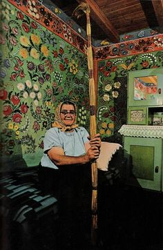 """A whole house for a canvas: Mrs. Lajosne Vargacz sits before a bedroom mural painted with the help of her neighbors at Kalocsa. Such folk art, once common in the region, today has few practitioners. Cane-and-feather duster resembles the long-handled paint brushes the artists used to decorate hard-to-reach heights."""