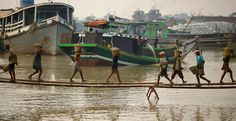 People carry baskets filled with sand at the bank of the Yangon River