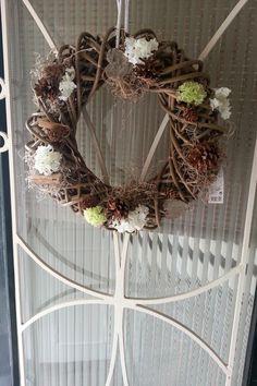 Foto: Krans opgemaakt met herfst accessoires, zoals houten hartjes…