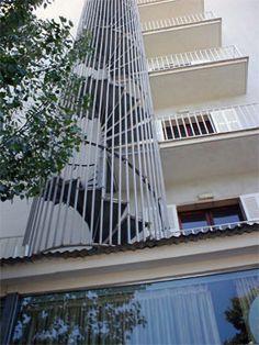 Escalera Caracol con enrejado de protección en exteriores a edificios.