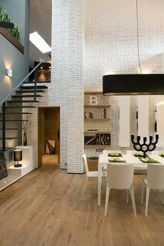 High ceilings, white brick walls and oversized black pendant light fixture brings scale together.