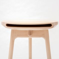 Wooden stool with a gaping mouth stores a magazine within its seat