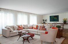 Linda sala de estar com sofá de cor neutra e detalhes laranja!