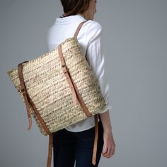 """Our popular market basket is now available in backpack form. Equipped with two adjustable leather shoulder straps, this charming basket is perfect for all you foraging aficionados! Handmade in Morocco by local artisans using dried palm leavesDimensions approximately 15""""tall x 13""""wide"""