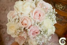 Hand tied bouquet of blush pink and ivory roses with gypsophila