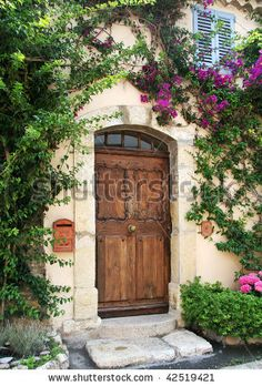Richly-grained wooden door to private stucco villa in medieval village of Mougins, France.  Flowering vines frame the doorway, and there's a classic blue-shuttered window above. by Karen Wunderman, via Shutterstock