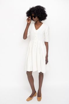 The Atelier Delphine Katelle Dress in creamlinen. Features v-neckline, unlined with half length sleeves, side pockets, button front closure and pleated fitt...