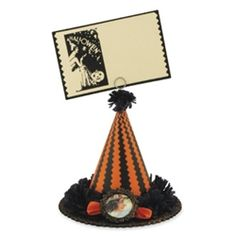"Witch Hat Card Holder and Placecard  Display your spookiest photos or use for a placecard holder. This delightful Halloween hat is made of pressed paper with a witch image and embellished with crepe paper fringe, tinsel, ribbon and glitter accents. 5"" x 4 1/2"". Includes card. A Casey Mack design for Bethany Lowe."