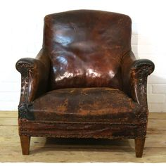 Distressed brown leather armchair for hire. Comfortable worn brown leather chair with solid wood legs. Great as a prop for photo shoots and events.