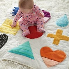 Our Shape Up Baby Activity Mat is filled with endless hours of exploration for the little ones.  It's topped with an array of shapes in vibrant colors and patterns.  The soft play mat is made from cotton canvas and extra comfy for babies to play on.  Designed exclusively for us by Ashley Goldberg.