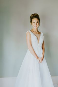 This whimsical wedding dress features a plunging v-neckline and embellishments on the shoulder and waist. The ballgown wedding dress skirt has layers upon layers of romantic gazar and English netting. #designerweddingdress #romanticweddingdress #bohoweddingdress #wedding #weddingdress #bride #bridalgown