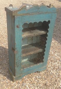 A vintage painted wooden cabinet, from Rajasthan,  With a glass door and two shelves.  In an attractive blue with a lovely scalloped edge around the