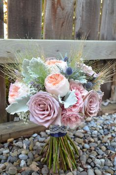 Country meadow inspired bridal bouquet with wheat, blue eryngium thistle, dusty miller, Juliet garden roses, pink spray roses and Amnesia lavender roses wrapped in navy blue satin ribbon with a lace overlay.  www.flowersbyjanie.com  Flowers by Janie-Calgary Wedding Florist