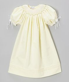 Styled so sweetly with puff sleeves and a smocked neckline, this classic confection of a dress features buttons in back for easy dressing and a pretty polish. Dainty bows on the gathered sleeves provide a delicate dusting of charm.