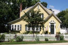 """A vinyl-sided box gets character and curb appeal with the addition of a white picket fence, a brick walk, flower boxes, shutters and cheery yellow paint. See the """"before"""" @ thisoldhouse.com"""