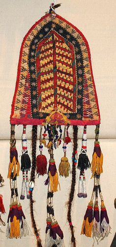 a 19th century Turkman fragment and has added blue beads, cowary shells, tassels, etc. This was to hang in one's tent or home.  It was purchased from the wall of a home.