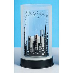 The City Skyline Centerpiece features a city skyline with star accents. Each of the 9 inch high city themed centerpieces has a 5 inch diameter glass cylinder that sits on a plastic base.