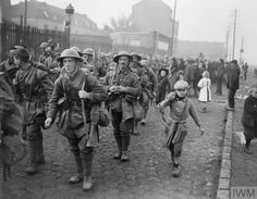 Men of the 57th (2nd West Lancashire) Division marching through the outskirts of Lille/Rijsel/Rysel accompanied by a young boy holding a rifle 18th October 1918. [OS] [800x623]