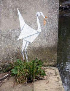 oragami crane with a fish - banksy
