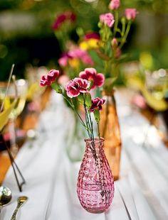 Vasos com flores miúdas é uma das dicas para enfeitar a mesa em um almoço no jardim