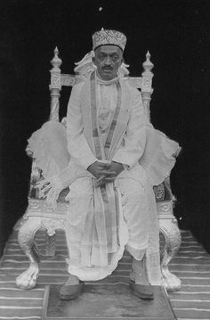"Narayan Maharaj seated on a silver throne, a gift from the King of Nepal.  It was on this throne that he seated Merwan Irani, the young Meher Baba ""dazed"" by Babajan's kiss, in 1915."