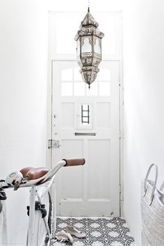 white entryway with moroccan light fixture.