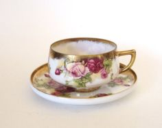 Here is a stunning Royal Sealy lusterware teacup and saucer set. The set has yellow on the bottom of the cup and the center of the saucer with a pink roses chintz pattern adorning the body of the teacup and the saucer. The saucer is reticulated, and has an open weave pattern. The gold around the edges of the saucer and the edges of the teacup has a splatter affect with gold in a diamond pattern on the teacup and a gold handle. I love the unique shape of the teacup. This is a very charming…