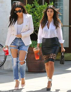 Kim Kardashian stepped out in heavily ripped jeans while sister Kourtney's leather skirt was punctured all the way up to her mid thigh