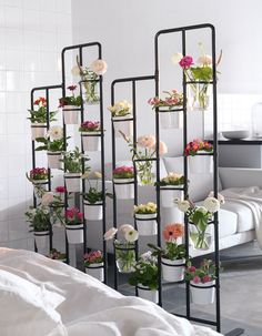 10 Examples Of Multi-Functional Room Dividers | A divider filled with flowers and plants is a great way to create separation between spaces and brightens up the whole area.