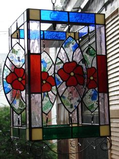 Spinner - A 4 sided open piece. The spinner is on a swivel as are all of the center pieces so they turn in the wind.  The surrounding frame is green on the bottom for grass and blue on the top for the sky. The middle is red to match the flowers.