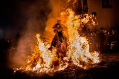 "A man rides a horse with a child through the flames during the ""Luminarias"" annual religious celebration on the night before Saint Anthony's, patron of animals, in the village of San Bartolome de los Pinares, about 62 miles northwest of Madrid, Spain, Jan. 16, 2014. According to tradition that dates back 500 years, people ride their horses through the narrow cobblestone streets of this small village to purify the animals with the smoke of the bonfires."