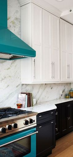 In this bright kitchen, designed by Elena Eskandari and Elle Hunter, classic black and white cabinetry were paired with natural marble countertops, oak flooring and an opal green range and hood. Bright Kitchens, Modern Kitchens, Kitchen Cabinets, Kitchen Appliances, Marble Countertops, Beautiful Kitchens, Oak Flooring, House Design, Black And White