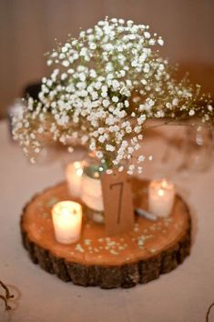 Rustic chic wedding centerpiece idea - baby's breath flower arrangement + votives on a wooden slice {Swanky Fine Art Weddings}