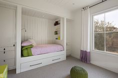 An alcove bed, with pull-out trundle bed underneath, flanked by built-in cabinets, gives this bedroom lots of open play space, and helps fight clutter...