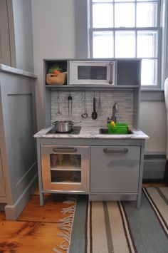 A play kitchen that matches the real kitchen. This Ikea play-kitchen was transformed using paint, contact paper, and vinyl tiles.