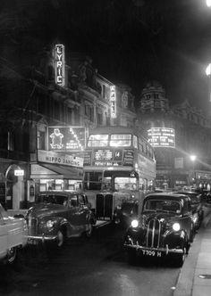Traffic travels down Shaftesbury Avenue in 1954 / London