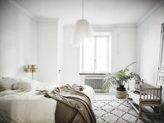 Swedish inspired bedroom with a large area rug, a metalic lamp and a indoor plant