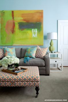 Tobi Fairley - Gorgeous living room with orange and green abstract art over modern taupe sofa beside Bungalow 5 Polo 1 Drawer Side Table topped with lime green lamp layered pillows paired with orange and blue ottoman as coffee table.