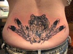 Wolf and feathers lower back tattoo.