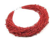 Naszyjnik wykonany ręcznie na bazie przędzy lnianej, w którą wpleciono koraliki szklane w odcieniu czerwonej barwy.  Długość naszyjnika około 49cm. Wykończenia posrebrzane.