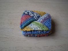 """Based on a traditional origami design, this little purse measures 5cm / 2""""². It opens up when you pull the top apart and then snaps back closed when you let it go. It is very simple to knit, the secret of the design lies in one purl row on each of the four sides and some serious blocking."""