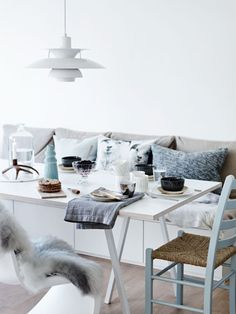 Arctic touch. Scandinavian dining table. Cool colors with warm textures. Sheepskin, cushions, etc