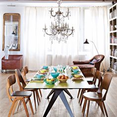 Dans la salle à manger vintage, autour de la table verte en acier et résine, créée par Igor-David Becker, le bois blond des chaises des années 50, Baumann et des modèles de cantine scandinaves des années 50, le lustre et le grand miroir doré tempèrent l'esprit industriel du plateau. Sur la table, vaisselle Pyrex des années 50.