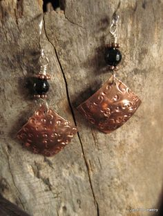 Tribal earrings are a textured copper diamond which dangles below a faceted black onyx bead . There are two copper spacers on each side of the bead and the earrings hang from a sterling silver ear wire. The length of the earrings including the ear wire is about two inches. The copper section of the earring is about three quarters of an inch. Onyx is believed to balance the yin and yang energies of the body. Copper is believed to help with circulation and amplify the properties of other…