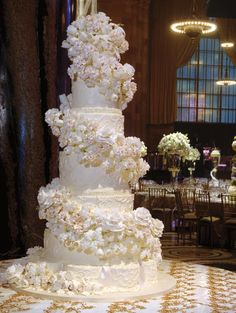 Beautiful multi-tiered white and champagne wedding cake with lovely embossed design on each layer... a spiral of champagne embossed tips on white eatable flowers. DS