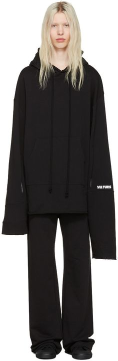 Long sleeve French terry hoodie in black. Asymmetric construction. Graphic printed in beige at hood interior. Tonal drawstring at hood. Kangaroo pocket at waist. Overlong sleeves. Vent at lower sleeves. Text printed in white and raw edge at cuffs. Pull-loop at back yoke. Raw edge at hem. Tonal stitching.