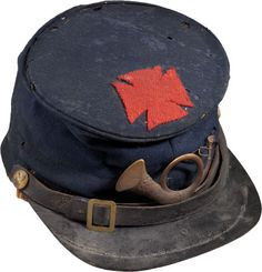 "Forage Cap with Original 5th Corps Badge. This is the standard Union Army issue ""bummers cap,"" first introduced in 1858 and symbolic of the Civil War soldier. Dark blue wool body, with its original chin strap, eagle side buttons. On the crown is sewn an original, hand cut, red wool 1st Division, 5th Corps badge and infantry horn insignia stitched on the front."