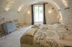 Lovely rustic bedroom with exposed stone walls in 6 bed holiday rental home Maison Jouas in South West France. Sleeps 12. www.purefrance.com