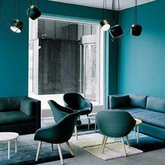 mur bleu canard, chaises bleues, sofas bleus rectangulaires, lampes style industriel