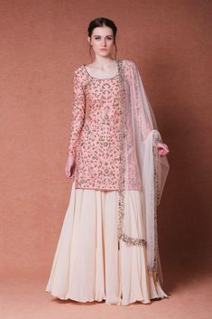 Featuring peach sharara suit with an embroidered kurta in chanderi base. Front, back, and sleeves of the kurta are embroidered with traditional Indian embroidery techniques using dabka, bugle beads, sequins and pearl beads. It comes with a beige flared kalidar sharara in crepe. Dupatta has an embroidered border and embellished bugle beads tassels on the four corners. Color: Peach/Beige Material: chanderi, crepe and net Dry clean only